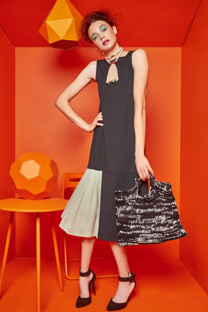 Stephanie wears the Moss Dress ($188), a sleeveless midi dress with a contrasting pleated panel, and the Tee Necklace ($58), paired with Kelly Lane's Texture Tote #1 ($138)