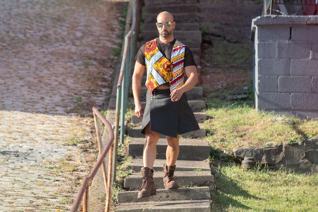 Hector Santos in an African wax print asymmetrical vest and a denim kilt